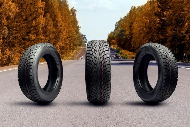 Três pneus de inverno em uma estrada de outono próxima substituição sazonal de pneus
