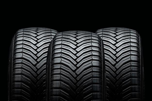 Três pneus de verão isolados em preto