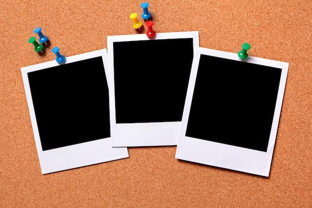 Três polaroids em uma placa de observação da cortiça