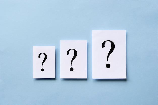 Três pontos de interrogação de tamanho diferente no cartão