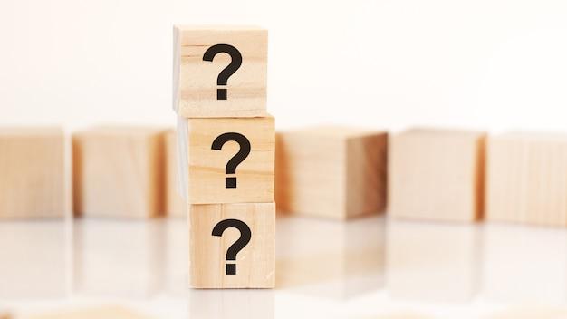 Três pontos de interrogação escritos em cubos de madeira, fundo branco