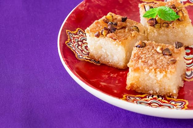 Três porções basbousa ou namoora - bolo tradicional árabe de sêmola doce com nozes, coco e água de flor de laranjeira. copie o espaço. espaço lilás.