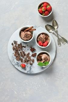 Três porções de sorvete de chocolate com chocolate, menta e morango