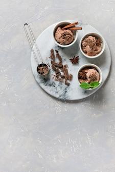 Três porções de sorvete de chocolate, decorado com chocolate e menta