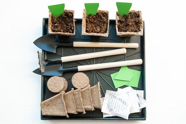 Três potes de turfa com rótulo vazio mock-se. como cultivar alimentos em casa no peitoril da janela. ferramentas para mudas e jardinagem em casa.