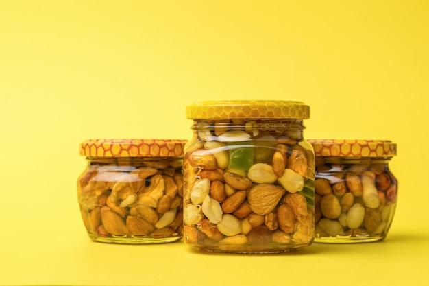Três potes de vidro com mel e nozes em um fundo amarelo. um remédio nutritivo natural.