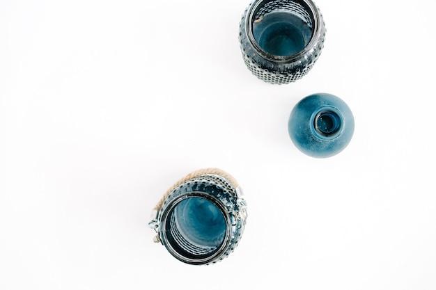 Três potes elegantes azuis sobre fundo branco. conceito de decoração mínima de vista superior.