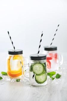 Três potes rústicos com limonadas caseiras frescas geladas de morango, laranja, limão, hortelã, pepino e água com gás, apresentados na mesa com gelo derretido ao redor