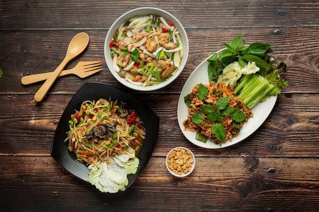 Três pratos de comida tailandesa picante colocados em chão de madeira