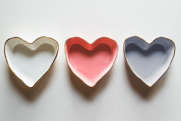 Três pratos de corações em um fundo branco em azul, vermelho e branco.