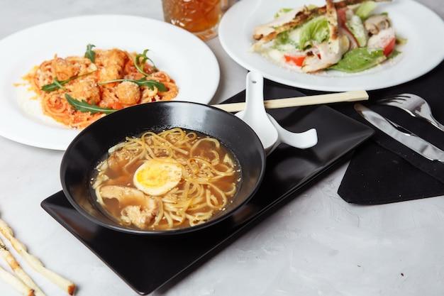 Três pratos definidos em uma mesa em um menu de restaurante, café. almoço de negócios em uma tigela de ramen com frango e ovo, salada caesar fresca e macarrão.