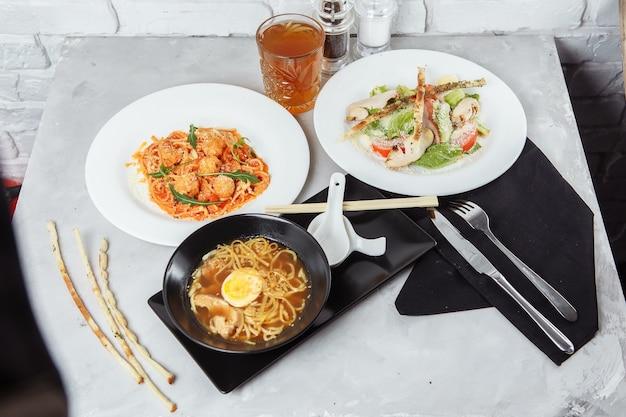 Três pratos servidos na mesa de um restaurante