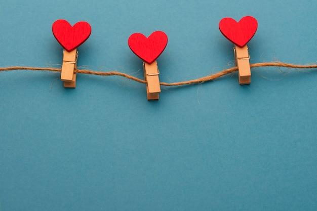 Três prendedores de roupa de madeira com um coração em uma corda