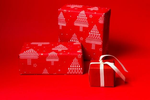 Três presentes embrulhados em papel vermelho festivo sobre fundo vermelho.