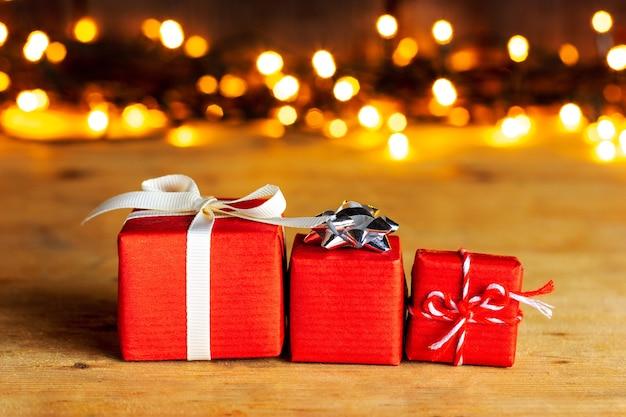 Três presentes vermelhos para um ente querido contra um fundo de luzes amarelas. saudações de feliz dia dos namorados.