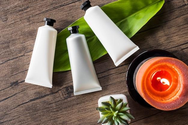 Três produtos cosméticos spa com vela acesa em fundo de madeira