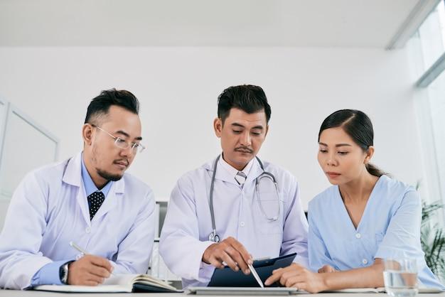 Três profissionais médicos masculinos e femininos discutindo a história médica do paciente