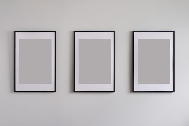Três quadros em branco na parede.