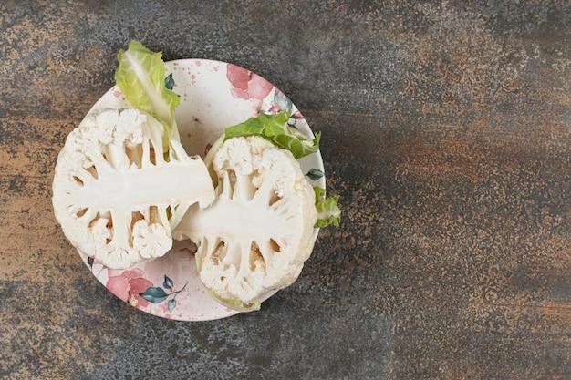 Três rabanetes no prato, na superfície do mármore