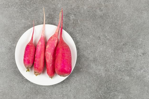 Três rabanetes vermelhos em prato branco