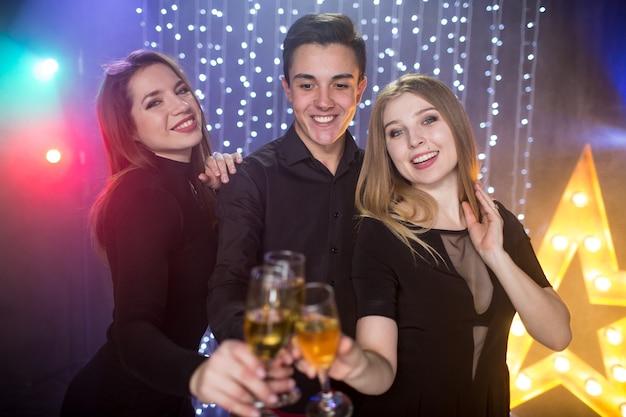 Três rapazes e duas mulheres com taça de champanhe comemoram um aniversário e se divertem em uma boate em uma festa