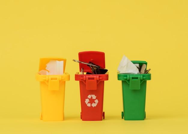 Três recipientes de plástico multicoloridos em uma superfície amarela, o conceito de classificação correta do lixo para posterior reciclagem