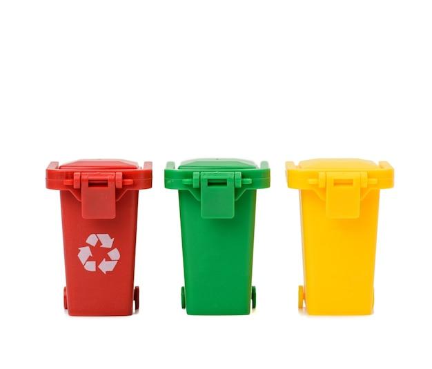 Três recipientes de plástico multicoloridos em uma superfície branca, conceito de classificação correta do lixo para posterior reciclagem