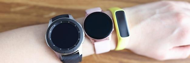 Três relógios de pulso diferentes são usados na escolha do close up da mão da mulher de pulseira de fitness