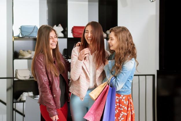Três rindo melhor griends indo às compras.