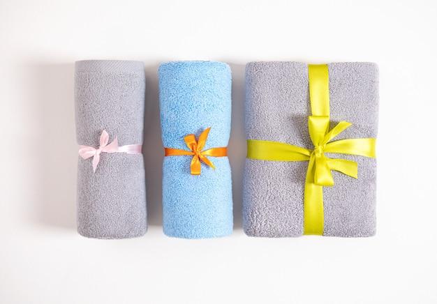 Três rolaram e dobraram toalhas de terry amarradas pela fita cor-de-rosa, alaranjada e amarela isolada. toalhas de terry azuis e cinzentas contra um fundo branco. vista do topo.