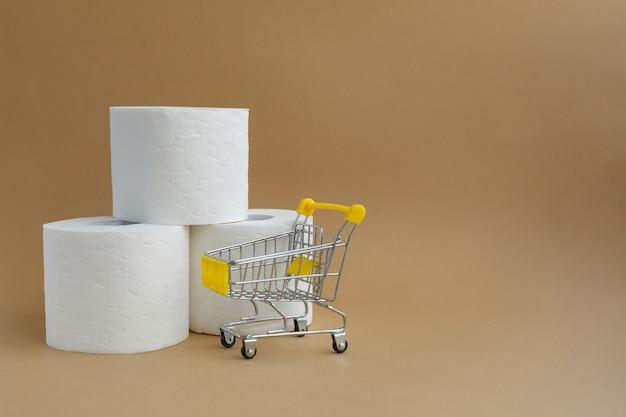 Três rolos de papel higiênico branco e um pequeno carrinho de supermercado