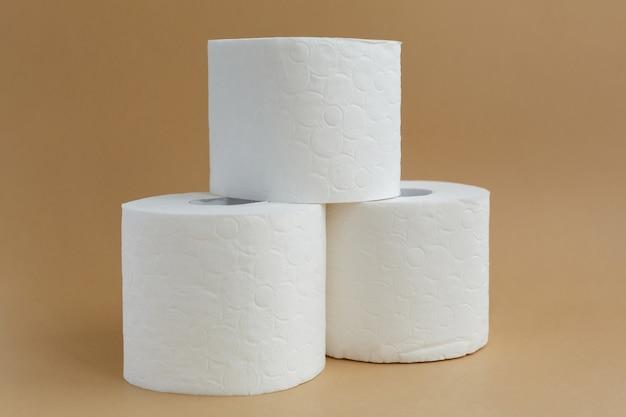 Três rolos de papel higiênico branco em fundo marrom