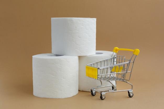 Três rolos de papel higiênico branco sobre fundo branco e um pequeno carrinho de supermercado