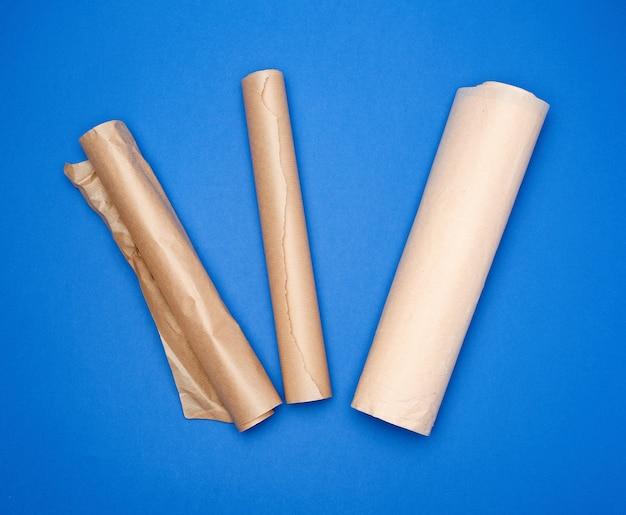 Três rolos laminados com papel manteiga marrom pergaminho em uma superfície azul