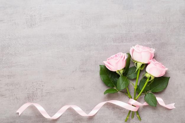 Três rosas cor de rosa e fita