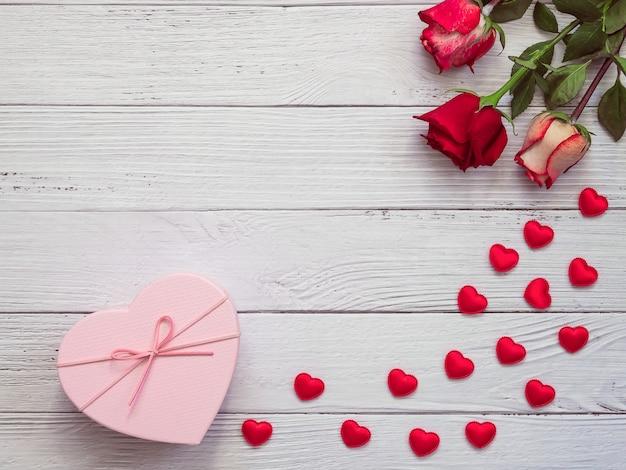 Três rosas e caixa de presente em fundo branco de madeira com corações