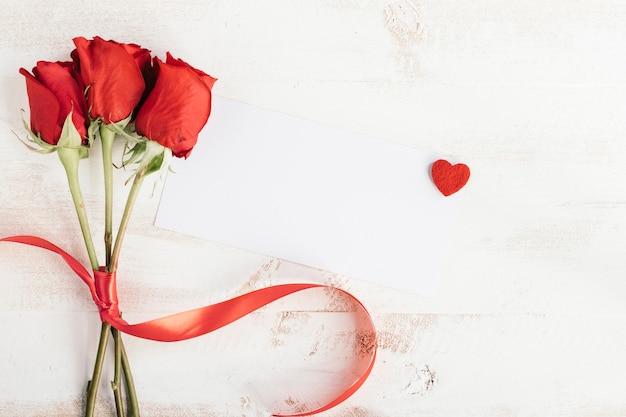 Três rosas e papel branco para mensagem