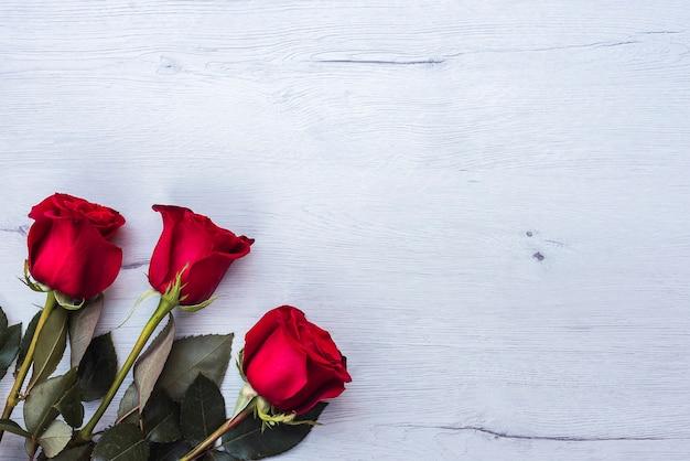 Três rosas vermelhas, na mesa de madeira, copie o espaço