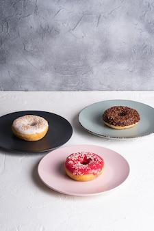 Três rosquinhas em pratos, rosquinhas de chocolate, rosa e baunilha com granulado, comida doce de sobremesa glaceada em concreto branco texturizado, espaço para cópia em ângulo