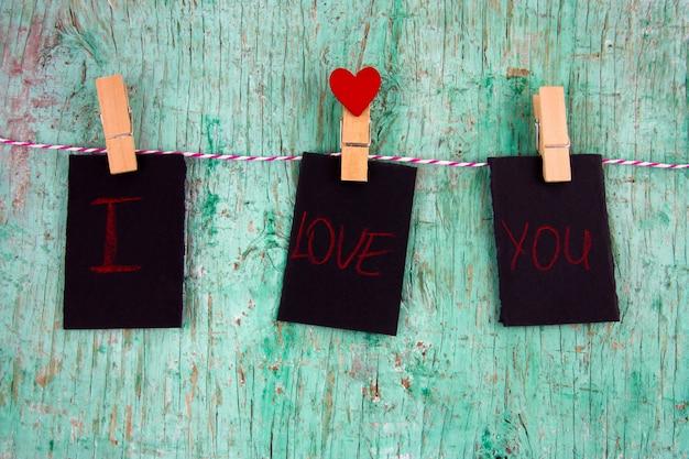 Três rótulos em branco com a inscrição eu te amo e coração de papel vermelho em pinos de pano pendurado em uma corda