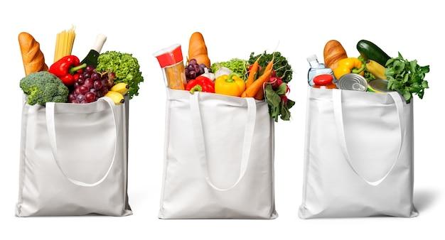 Três sacolas brancas com diferentes alimentos, frutas e vegetais