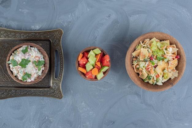 Três saladas em três tigelas na superfície de mármore.