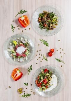 Três saladas nas placas de vidro na tabela de madeira clara em um restaurante. ingredientes na guia