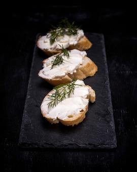 Três sanduíches com creme de queijo branco sobre uma fatia de pão
