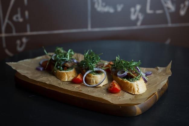 Três sanduíches de pão branco com patê de carne com anéis de cebola roxa com rúcula e fatias de tomate vermelho fresco em uma placa de madeira em um restaurante. comida saudável e saborosa