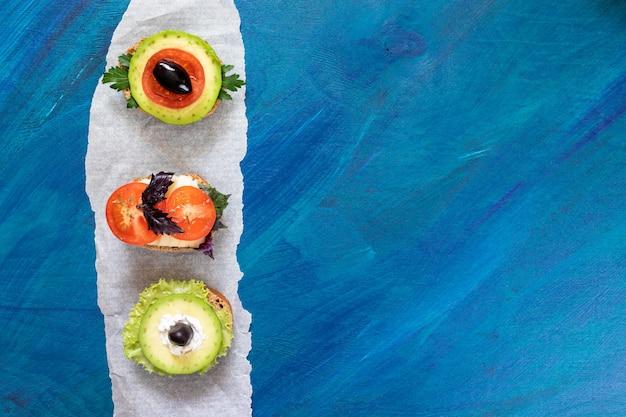 Três sanduíches vegetarianos em pedaço de papel de pergaminho vertical