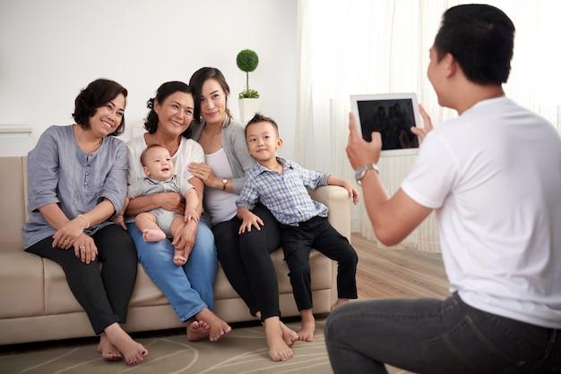 Três senhoras asiáticas com menino e bebê sentado no sofá e homem tirando fotos no tablet