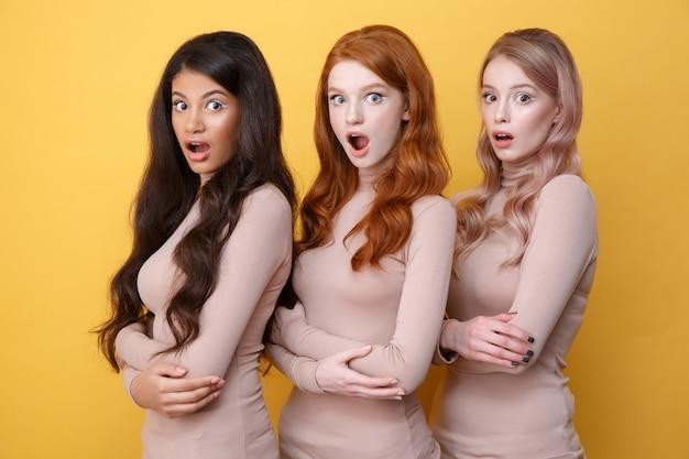 Três senhoras chocadas com os braços cruzados, posando no estúdio
