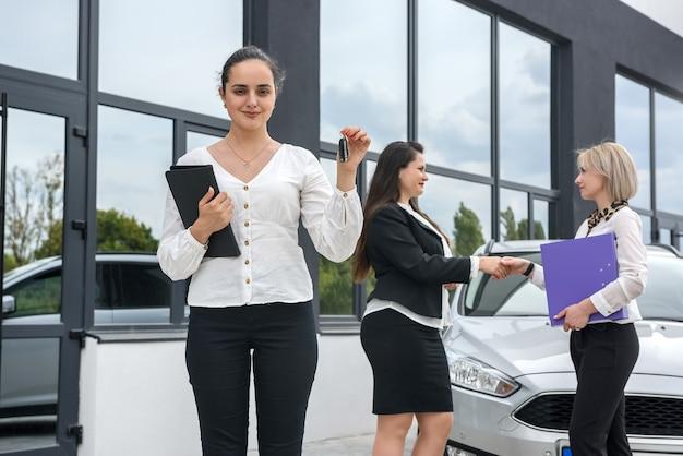Três senhoras com pastas em pé ao ar livre perto de um carro novo
