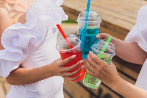 Três senhoras torcendo com saborosos néctares com cubos de gelo com palmas de palmas pretas decoração na piscina transparente limpa água azul clara sol brilha pele bronzeada lisa modo festivo despreocupado
